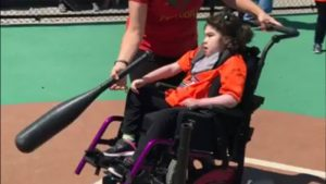 Child in wheelchair playing baseball