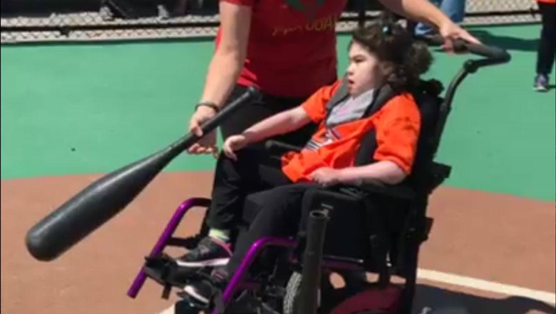 Child in wheelchair playing baseball