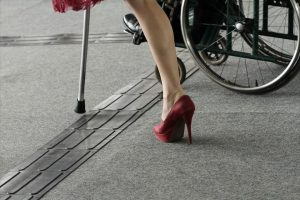 woman walking with cane next to person in wheelchair