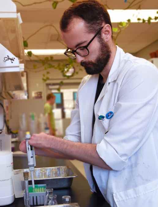Kyle Card inspects a petri dish.