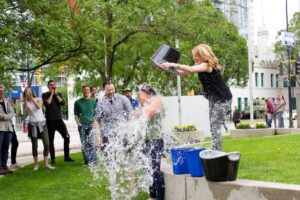 A woman in a park pours a bucket of water during a charity challenge