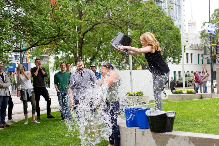Picture of a woman dumping a large bucket of water onto another woman.