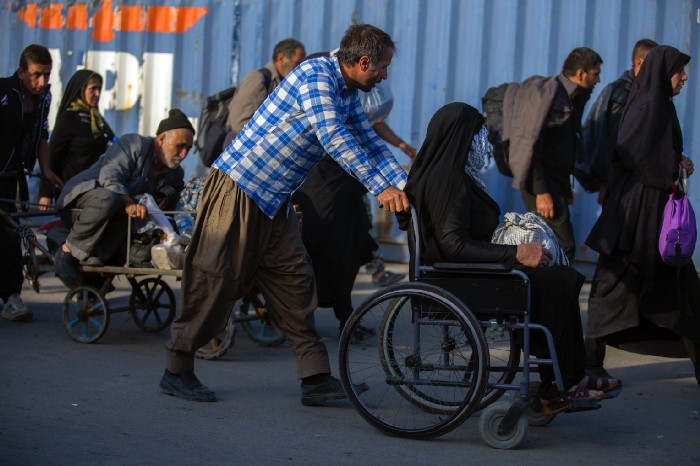 Picture of a man pushing a woman in a wheelchair.