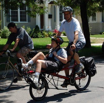 Man and younger disabled person bicycling on an adaptive bicycle.