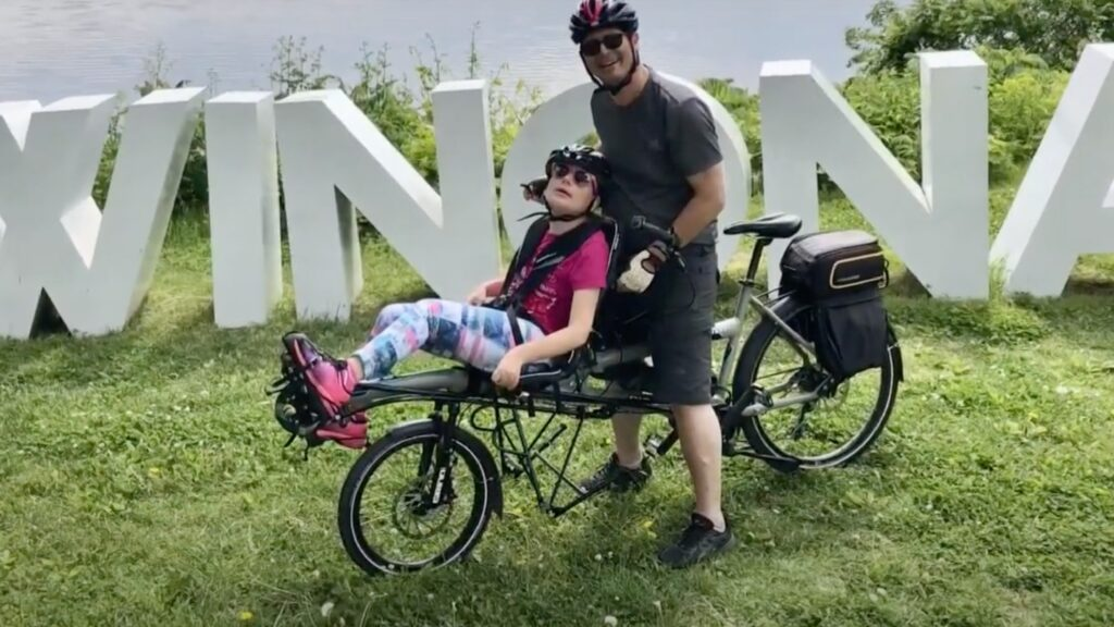 Ron with Daughter on an adaptive bike