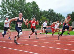 Multiple men running a race with prosthetic legs.