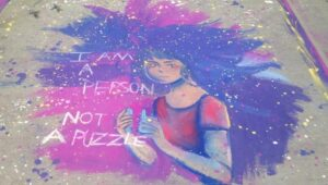 """A chalk art drawing of a women with blue and purple hair that says """"I am a person, not a puzzle""""."""