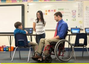 Picture of two kids talking to a man in a wheelchair.