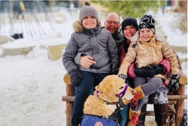 Picture of Kat Anderson and family, clockwise from left: daughter Poppy, dad George, mom Kat, son Atlas, and Atlas' service dog.