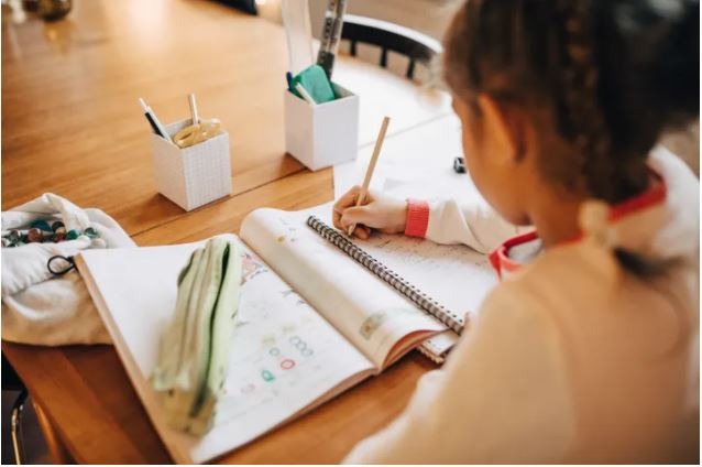 Picture of a young girl doing home schooling.